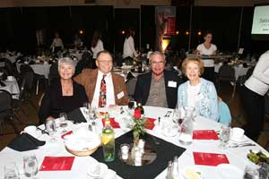 Photo of people gathered at a table during the Alumni Association Homecoming Banquet