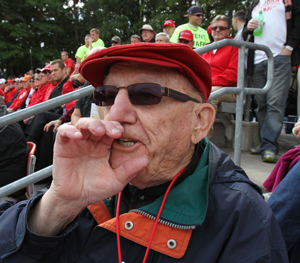Photo of Fr. Wilfred in the stands at SJU cheering for the Johhnies