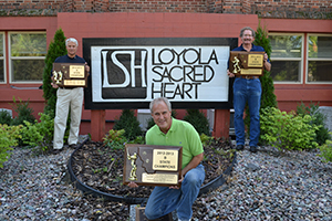 Phot of Matt Stergios '78 (l), Dave Klein '81 (c) and Dan Weber '72 (r) with the school sign at Loyola