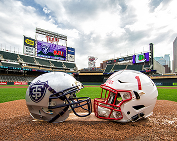 Photo of a UST and SJU football helmet facing each other on Target Field