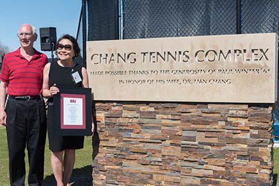 Photo of Paul Winter and his wife, Dr. Lian Chang by the Change Tennis Complex sign